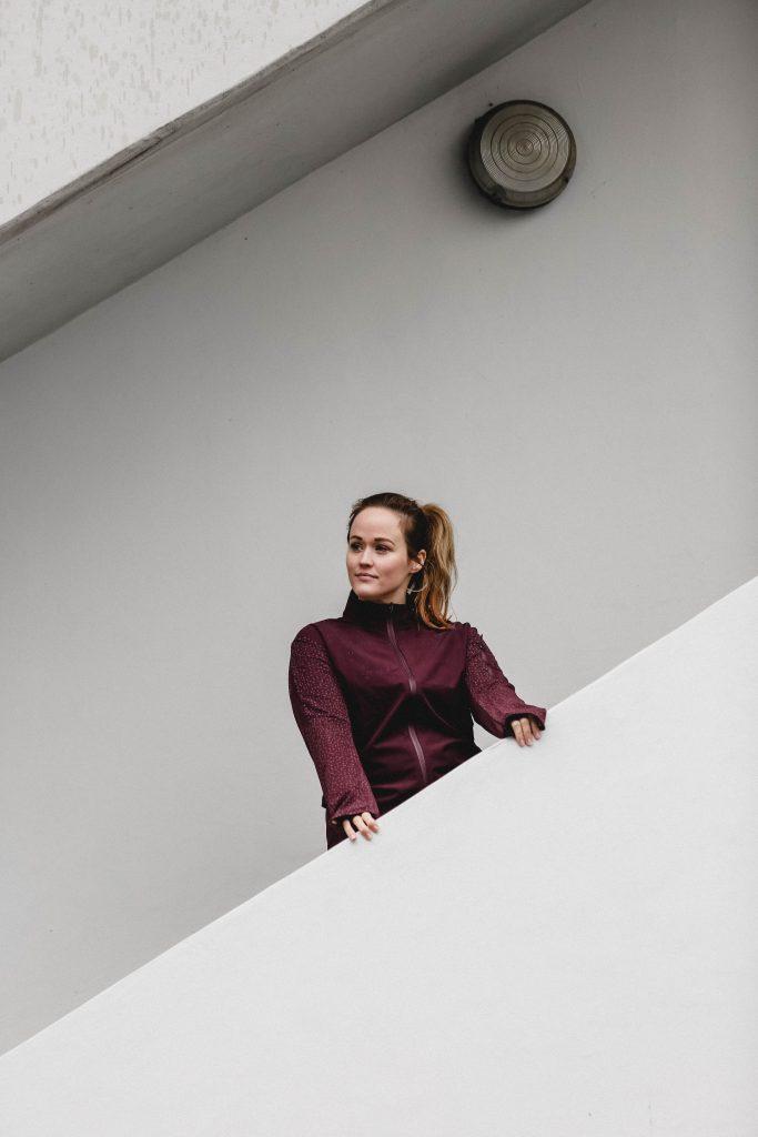 Jen steht auf einer Treppe im Running Outfit von Adidas