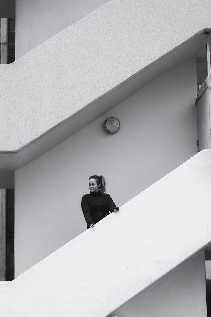 Bild in schwarz-weiß. Jen steht auf einer Treppe im Running Outfit von Adidas