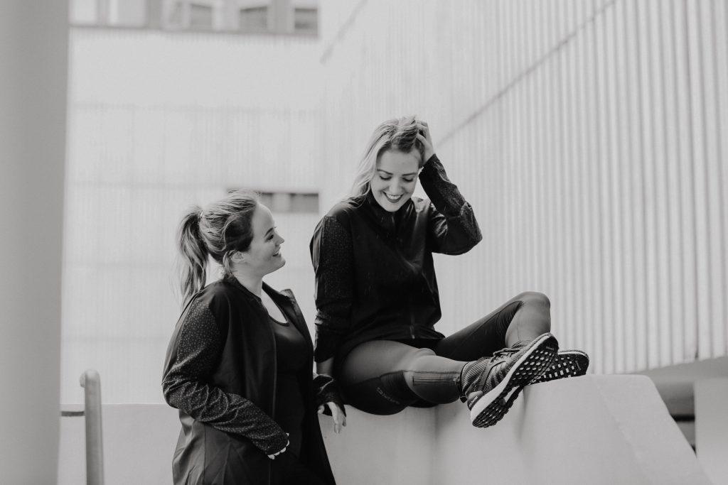 Die Gründerinnen Laura und Jen zusammen im Sportoutfit von adidas in Schwarz weiß