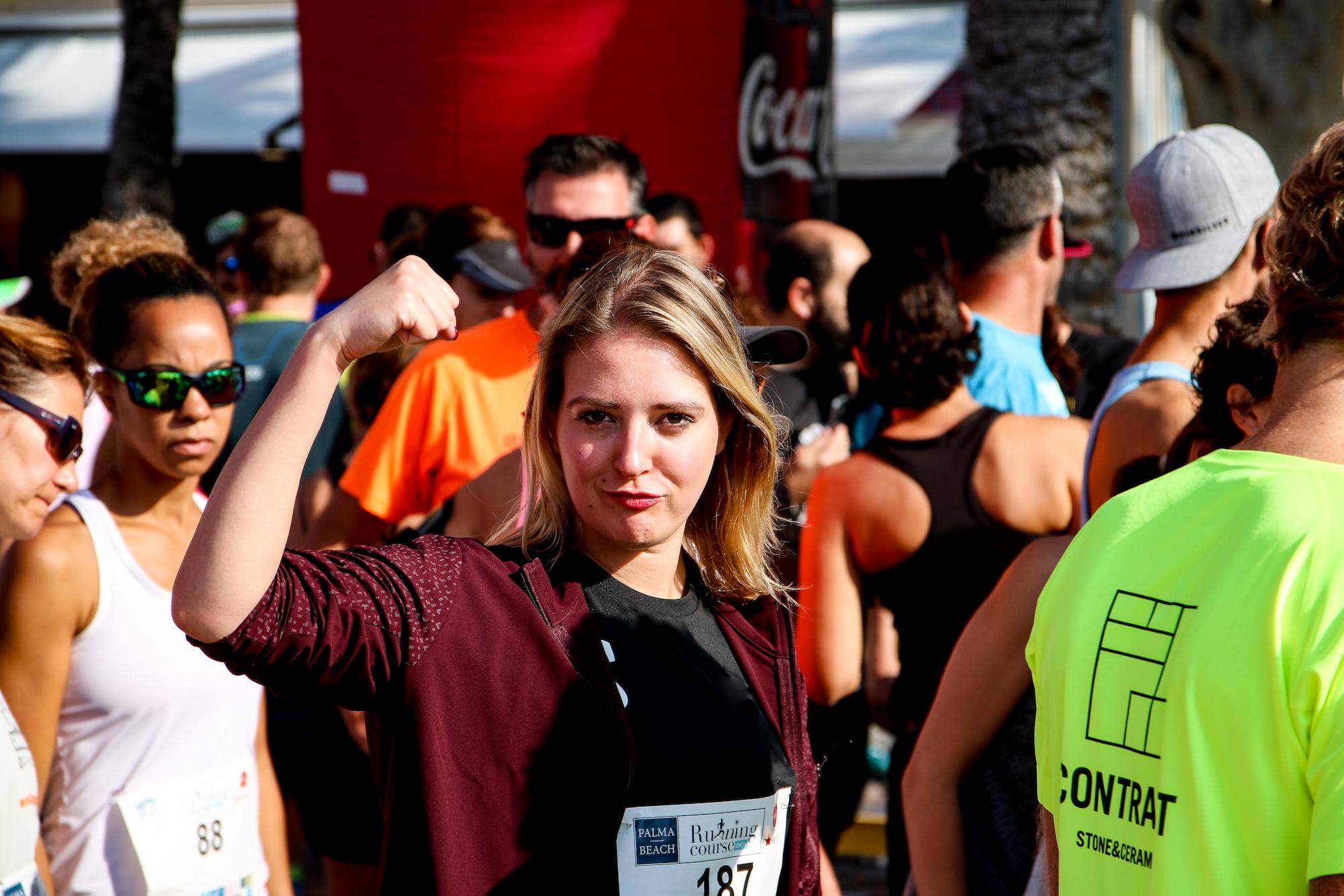 Laura hält triumphierend die hand hoch beim Palma Beach 10 Kilometer Lauf
