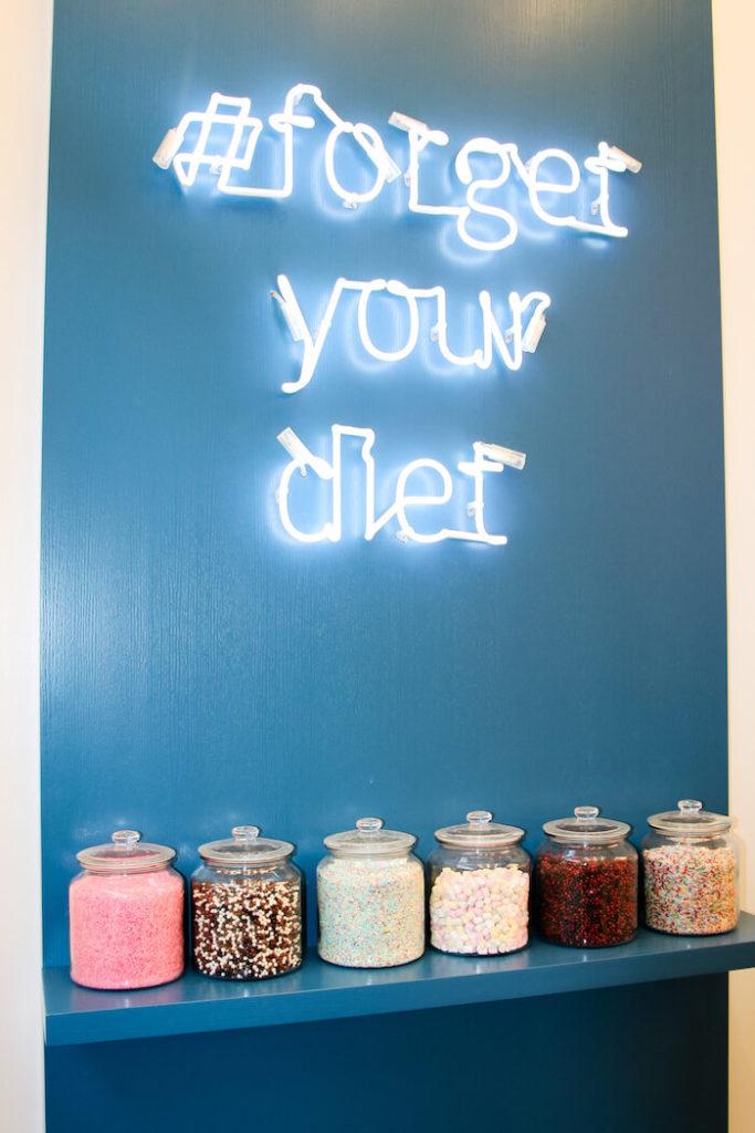 Eine blaue Wand mit dem Logo Forget your diet im Spooning Cookie Dough Laden in Berlin Mitte