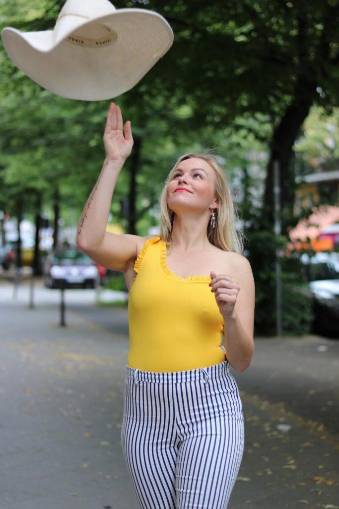 Sommer Outfit mit dem Bumble x SWIM WITH MI Badeanzug.Hannah schmeißt den Hut in die Luft.