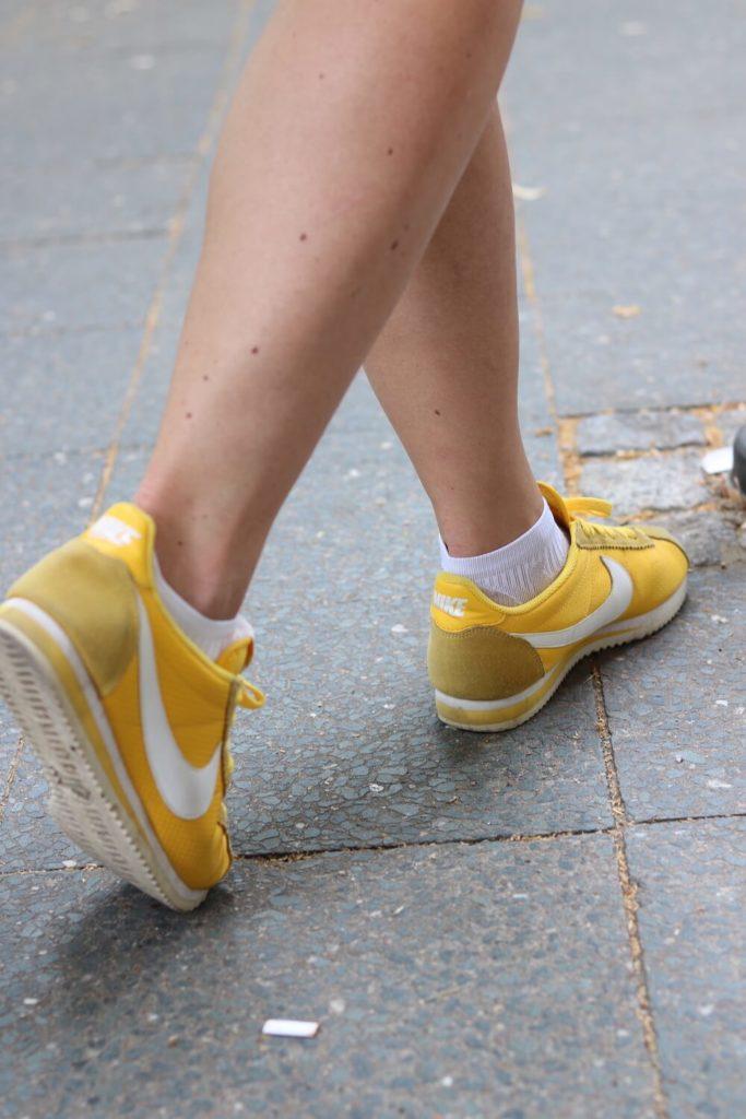 Sommer Outfit mit dem Bumble x SWIM WITH MI Badeanzug. Detail auf die gelben Nikeschuhe.