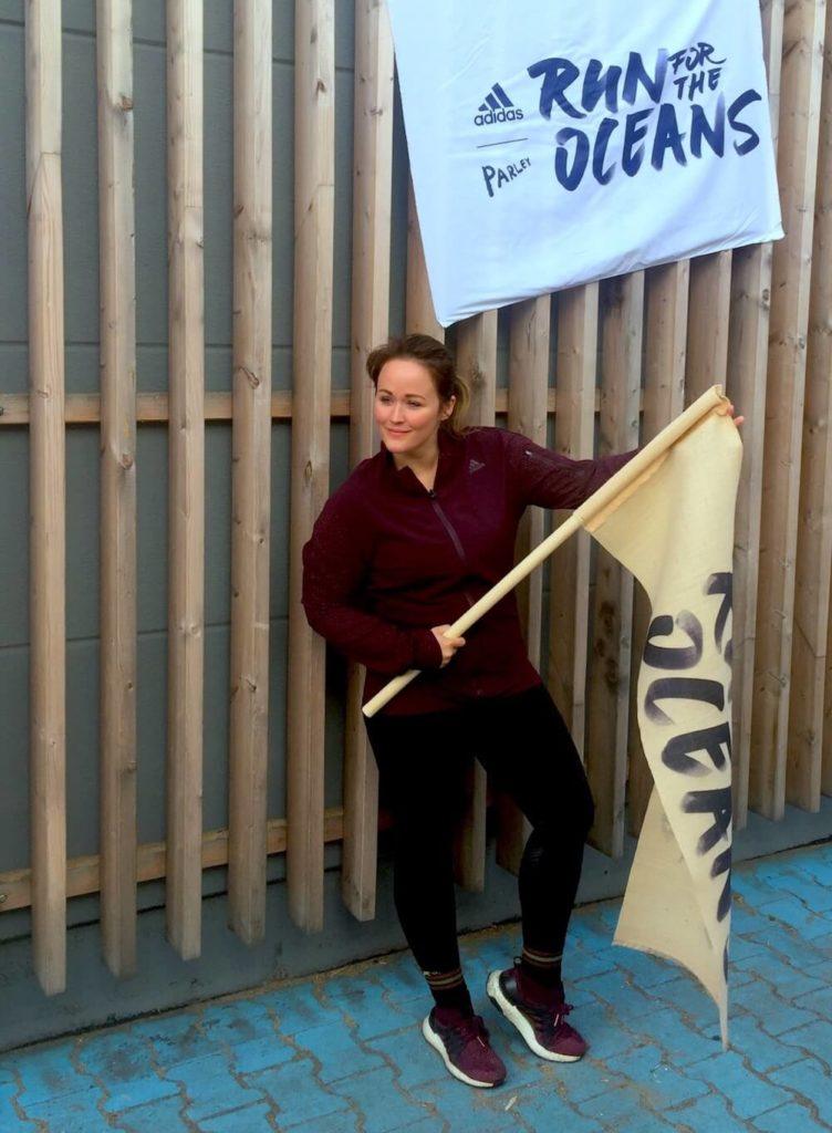 Der Run for the Oceans von adidas x Parley in Berlin. Im Bild Redakteurin Jen mit einer Fahne.