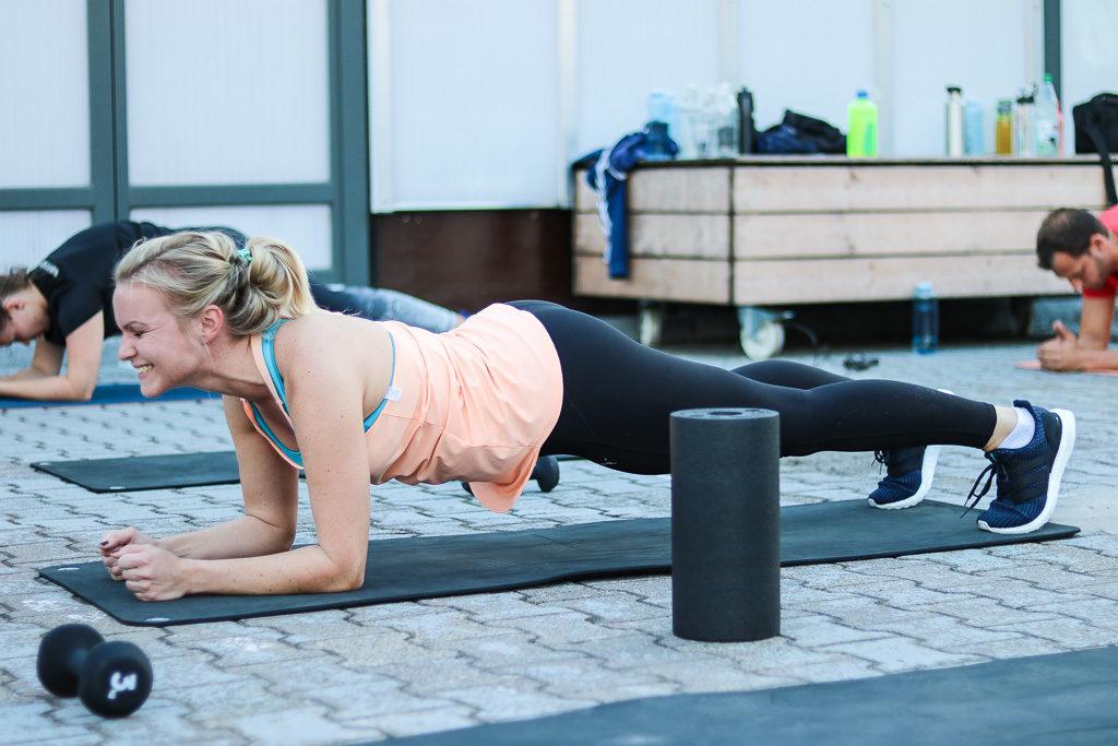 Junge Dame lacht beim Planken bei der 6 Wochen Challenge