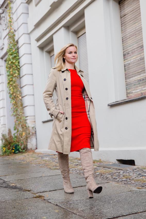 Business Frau Hannah trägt ein rotes Kleid des nachhaltigen Modelabels J.Jackman mit einem Mantel von Burberry und Overknee Stiefeln
