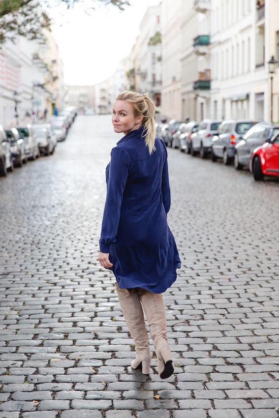 Business Frau Hannah trägt ein blaues Seidenkleid des nachhaltigen Modelabels J.Jackman Rueckenansicht