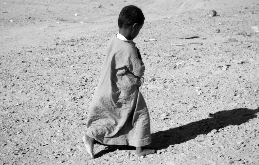 Menschenrechte kleiner Junge im Sand Barfuss