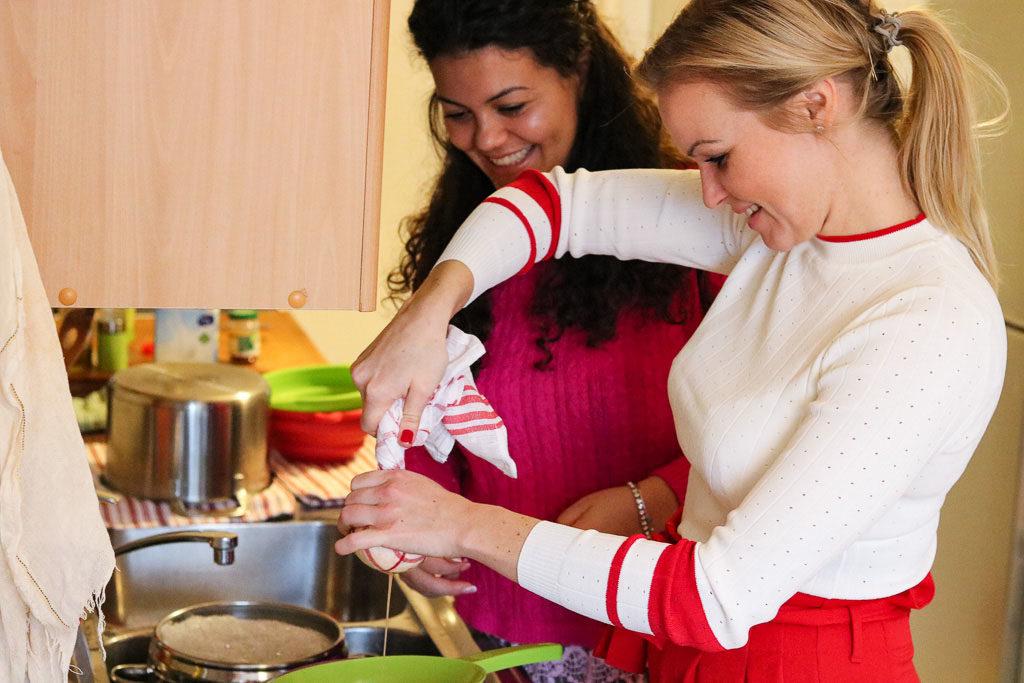 Hannah und Klarida von der besten Airbnb Entdeckung in Berlin beim Käse abschroepfen