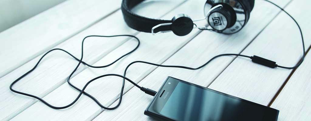 Handy und Kopfhoerer zum Podcast hoeren