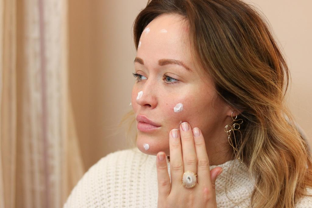 Tipps und Tricks zur optimalen Hautpflege mit Dr. Barbara Sturm. Ein Bild von Redakteurin Jen, die eine Kreme aufträgt.