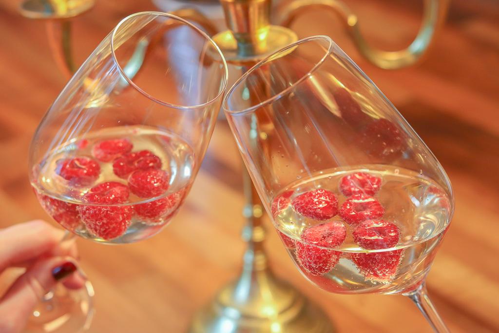 Rezeptidee fuer Valentinstagsmenue anstossen mit Sekt und Himbeeren