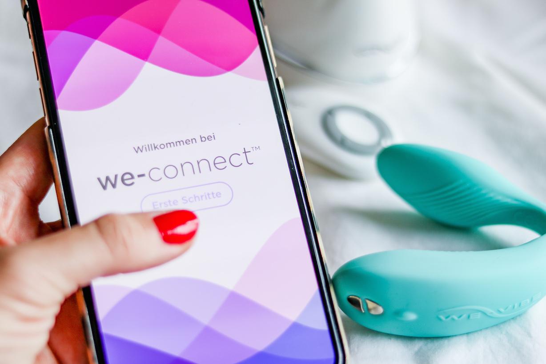Die We-Vibe Sync App we-connect fuer Sex in Fernbeziehung ist auf dem Handy geoeffnet. Im Hintergrund der We-Vibe Sync in tuerkis
