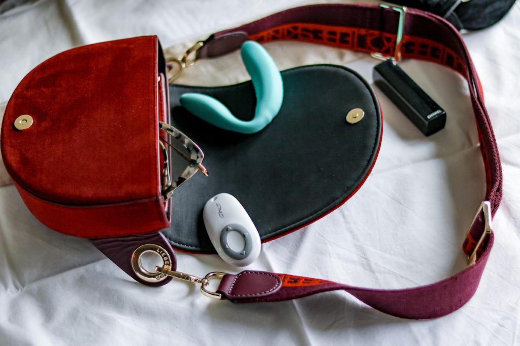 Der We-Vibe Sync in tuerkis liegt in einer Handtasche ausgebreitet