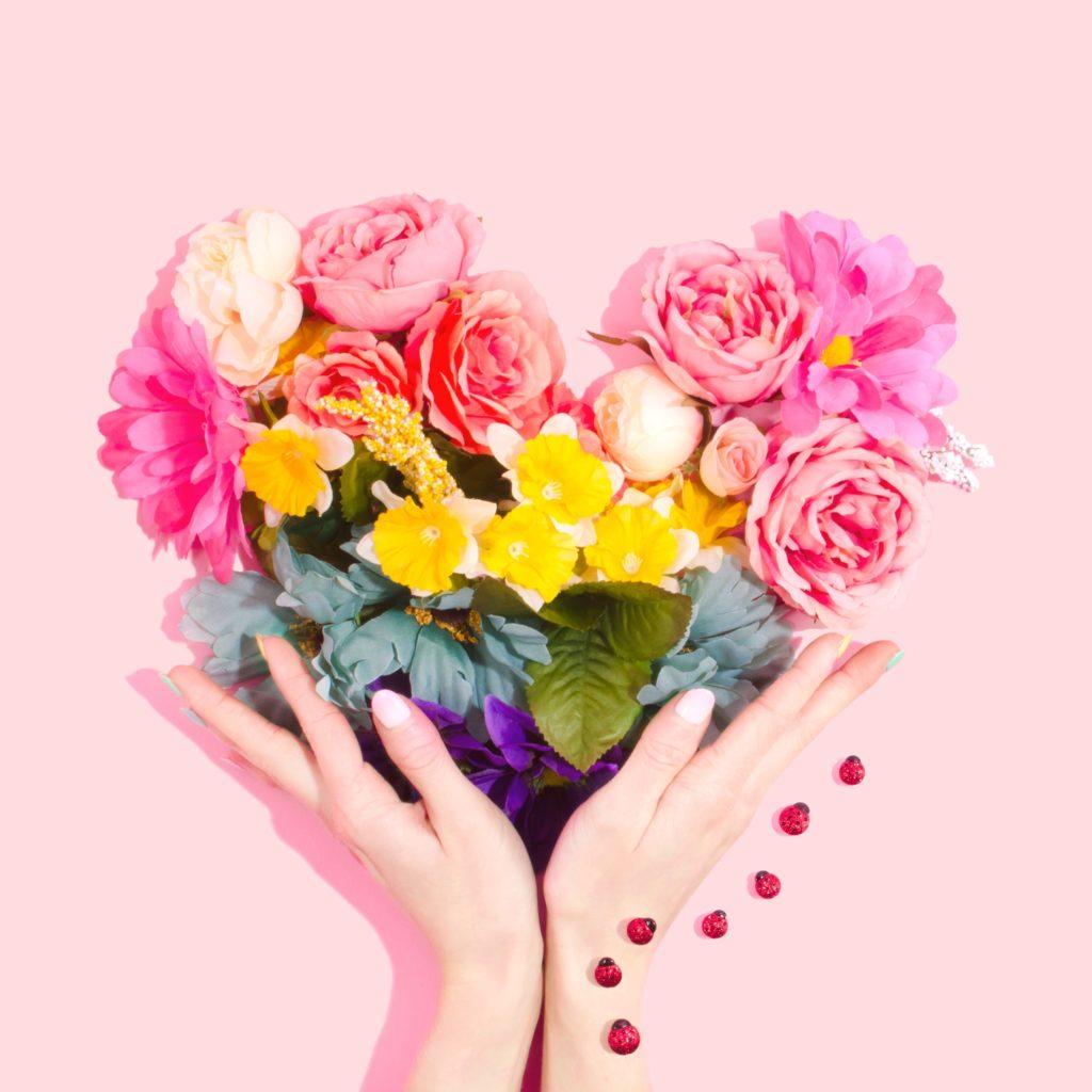 Blumenstrauß in Form eines Herzens der von zwei Händen gehalten wird