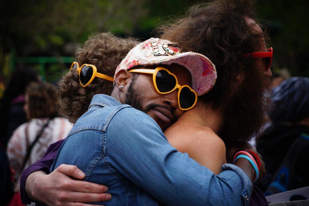 Drei Menschen die Sonnenbrillen in Herzform tragen und sich umarmen