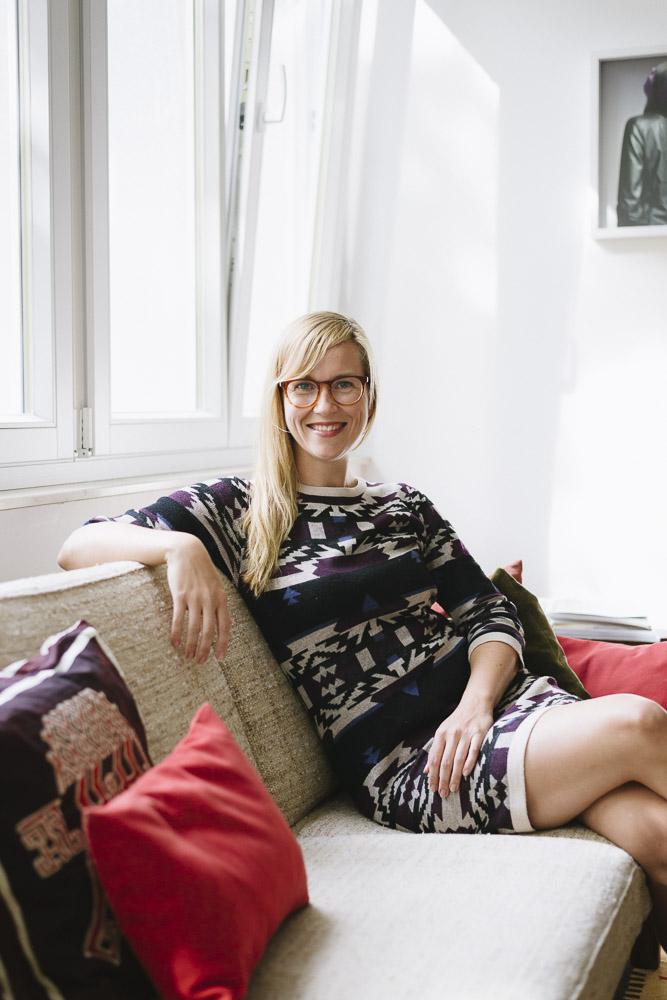 Berta Heide sitzt lächeld auf dem Sofa