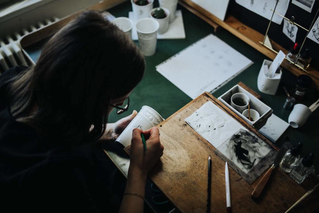 Porzellan Herstellung in der KPM Berlin. Der Königlichen Porzellan Manufaktur. Eine Malerin bei der Arbeit.