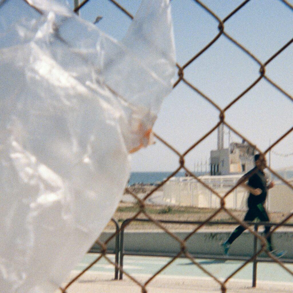 Jogger im Hintergrund gegen die Plastikverschmutzung für Run for the Oceans mit Plastiktüte im Vordergrund
