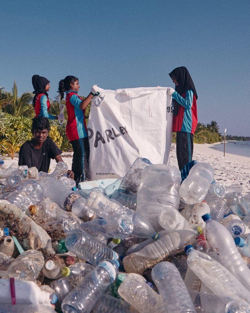 Jugendliche sammeln Plastikflaschen am Strand für Run for the Oceans
