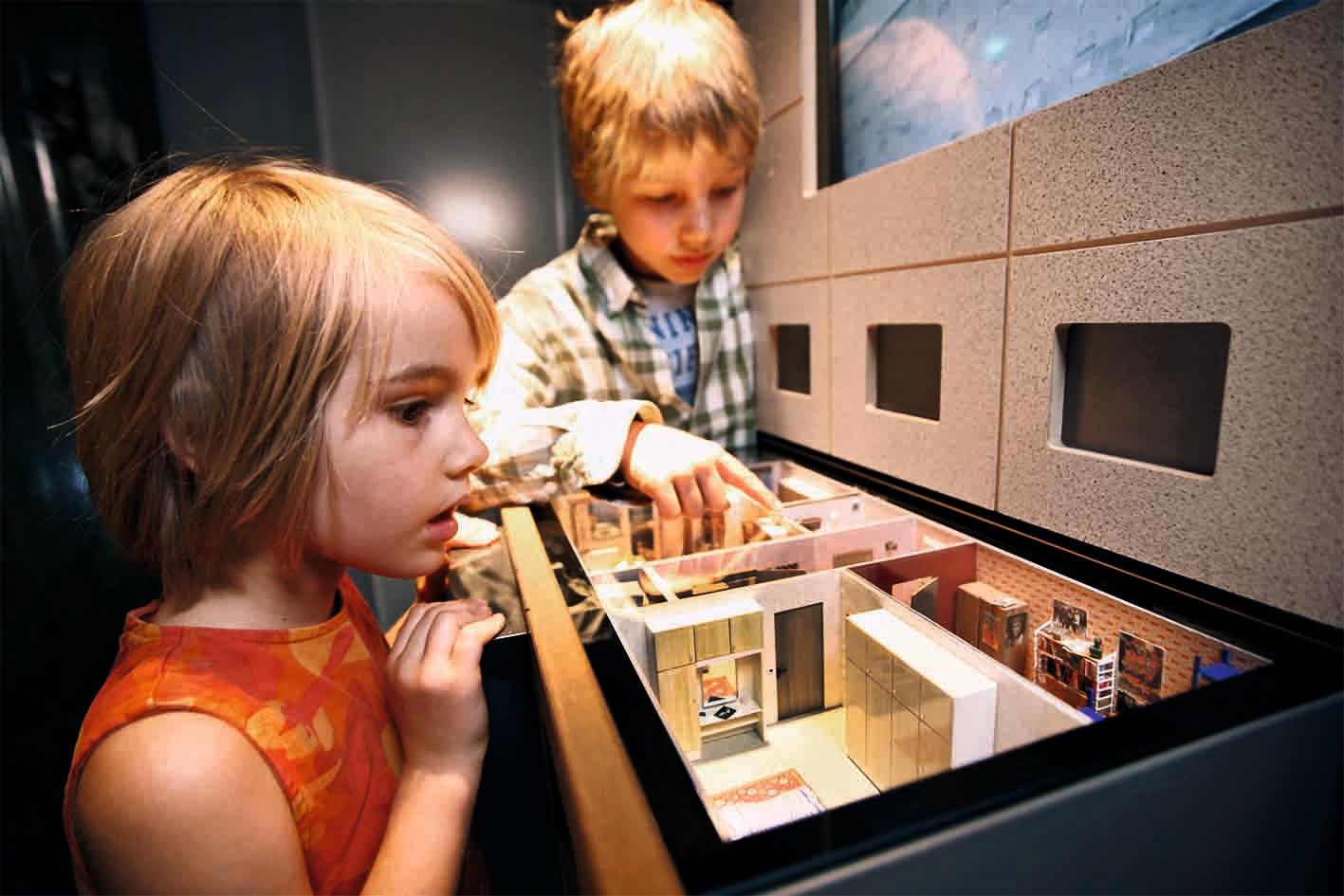 Kinder schauen sich ein nachgestelltes Wohnzimmer aus DDR Zeiten an