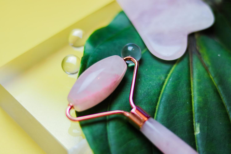 Ein Rosenquarz Roller und Gua Sha Stein zur Gesichtsmassage und Pflege.