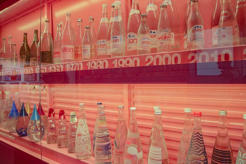 Eine Zeitreisetafel der verschiedenen Evian-Flaschen. Es gibt Mehrwegflaschen und Einwegflaschen aus Glas und aus PET und nun auch aus rPET.