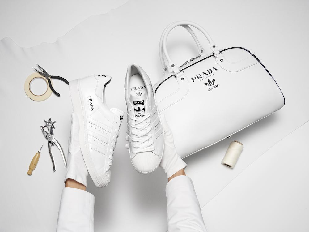 Die neue Zusammenarbeit von Adidas und Prada. Ein weißer Sneaker und eine weiße Bowlingbag.