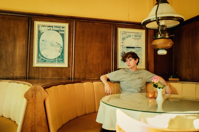 Junge sitzt im Cafe und traegt ein Thirt des Modelabels Habibi