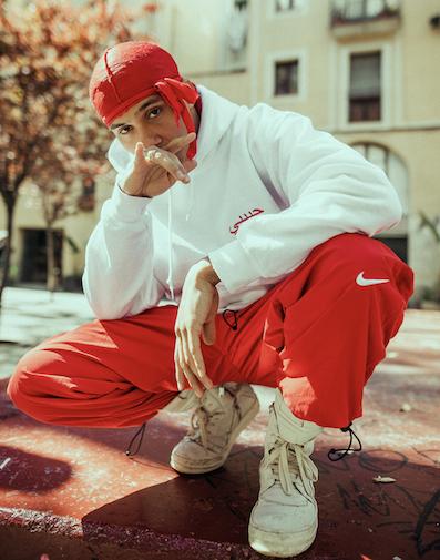 Rapper kniet und traegt einen rot-weissen hoodie des modelabels habibi