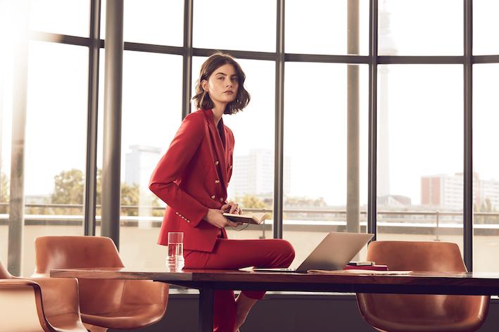 Busines Frau im roten Blazer von This is Her sitzt auf Arbeitstisch