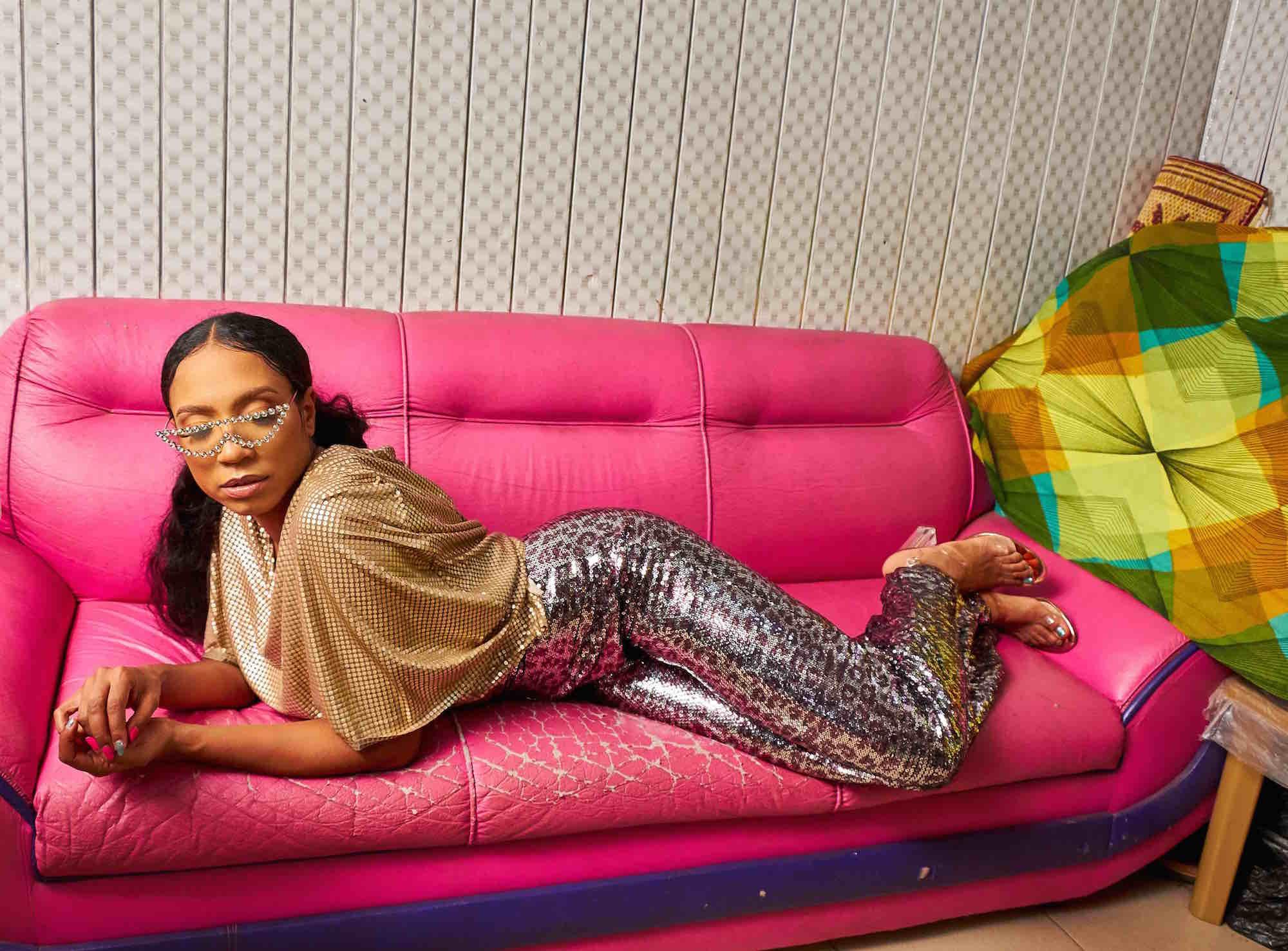 Saengerin Yakoto liegend auf einem pinken Sofa