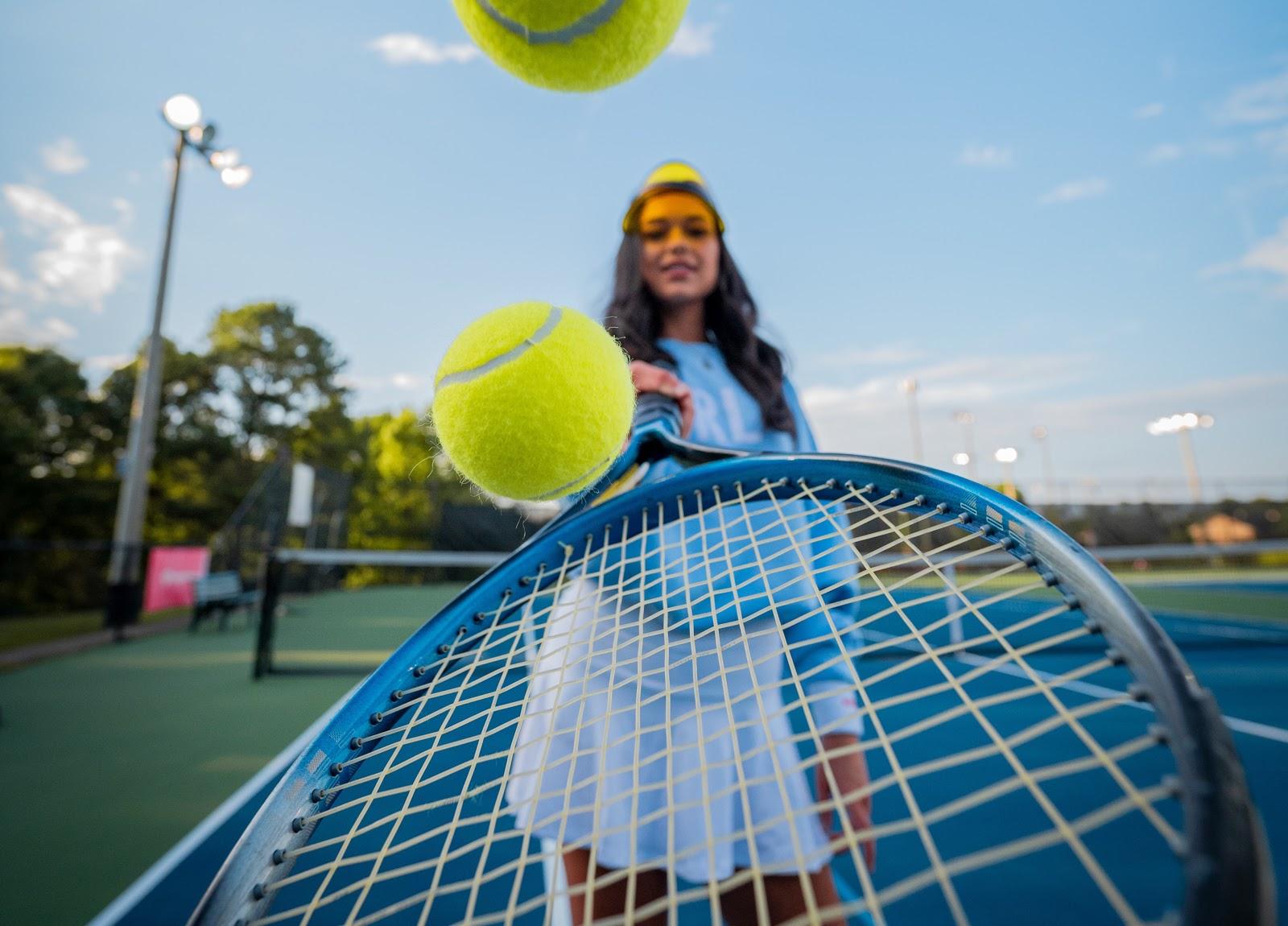 Frau mit Tennisschläger und hüpfenden Bällen